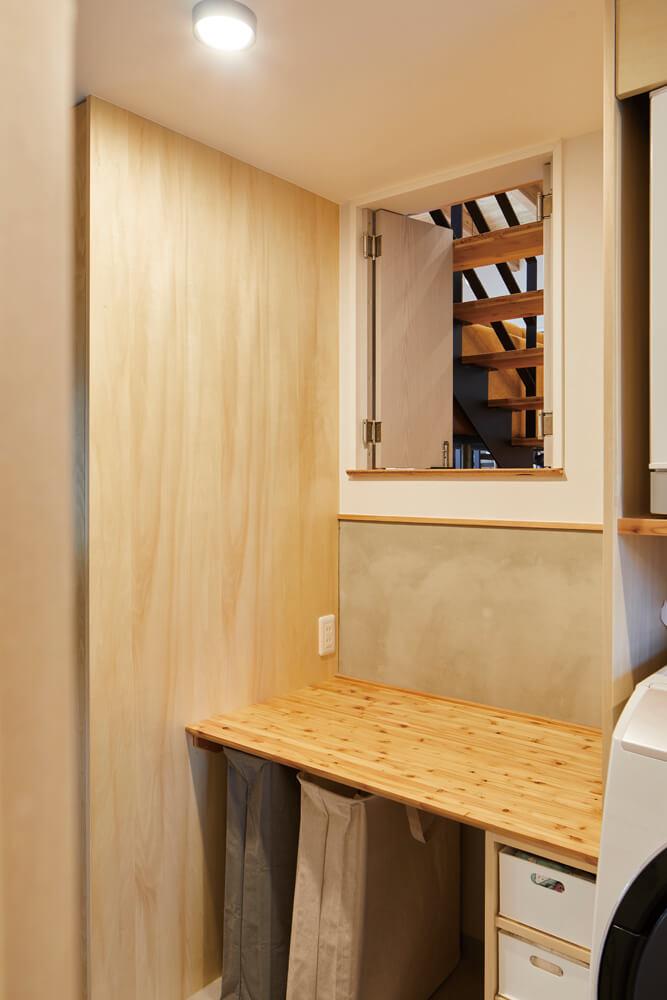 洗濯機の横には、アイロンかけや洗濯物を畳むのに便利な造作カウンター、両開きドアを採用した小窓を設置