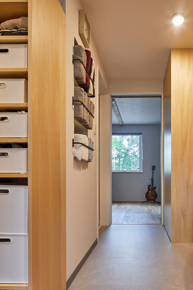 ユーティリティは、寝室への動線も兼ねている。空間に何通りもの機能を持たせることで、限られた床面積にゆとりを生み出した