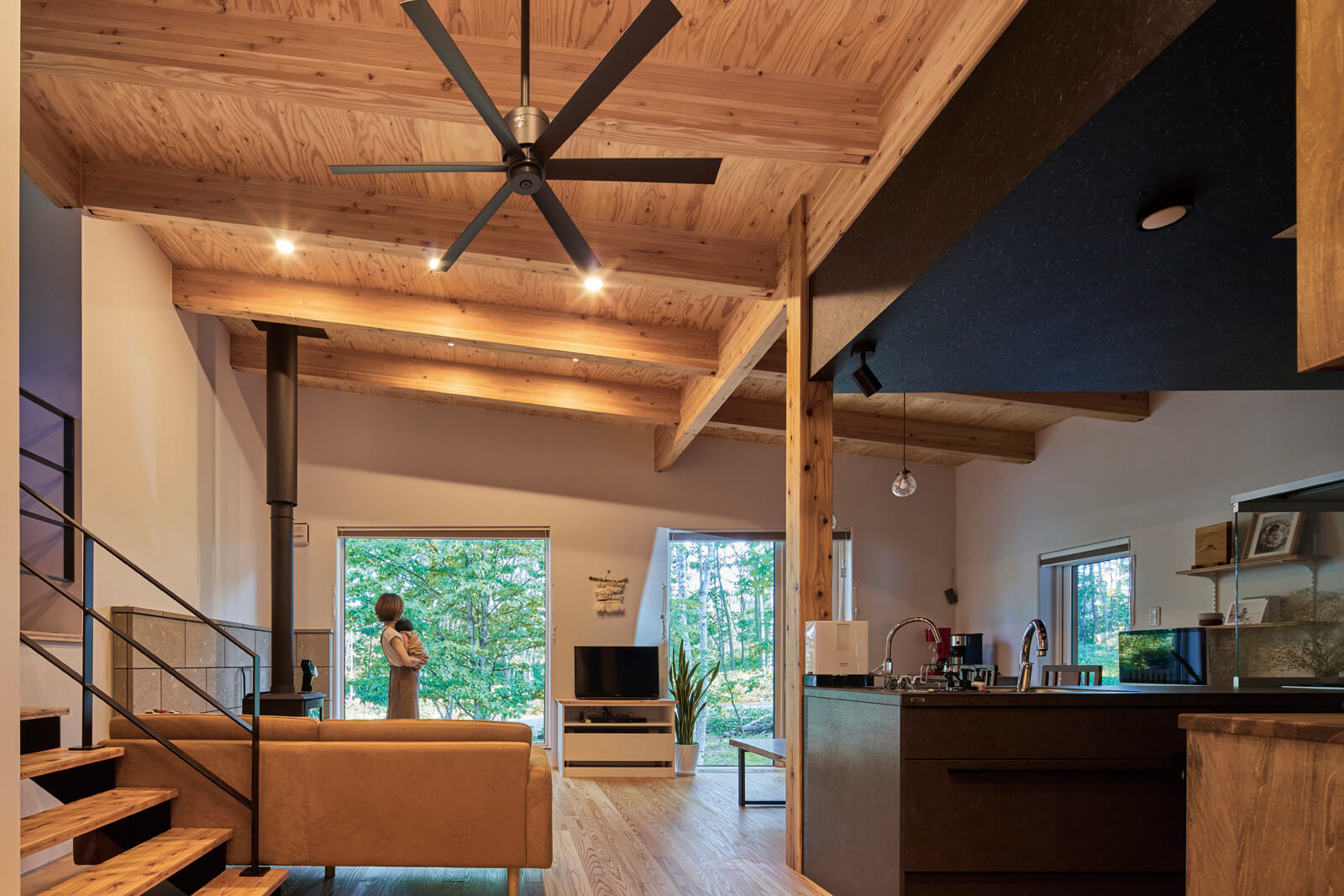 水野建設の提案で天井現しにしたリビング・ダイニング。素地仕上げの材と道産カラマツの床、大開口から染み込む木々の緑が、家族団らんの場に自然の息吹を運ぶ